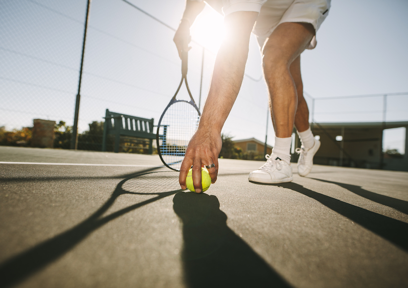 Ground,Level,View,Of,A,Man,Picking,A,Tennis,Ball